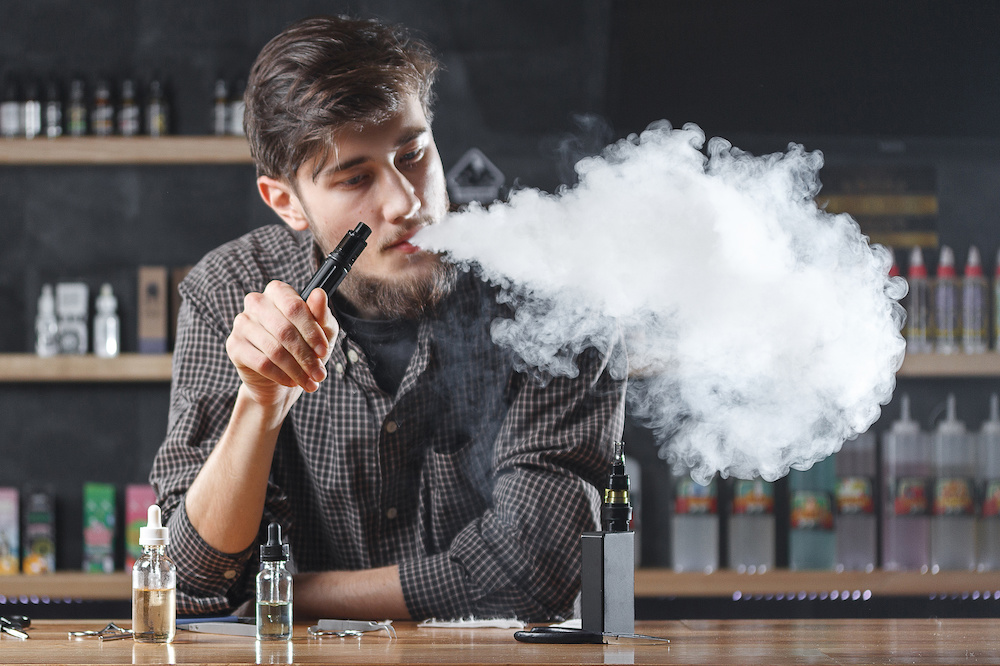Vape. Vaping man in a cloud of vapor. Photo is taken in a vape bar ( shop ).
