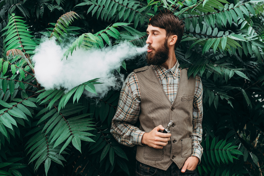 Young man with beard vaping an electronic cigarette outdoor. hipster smoke vaporizer.
