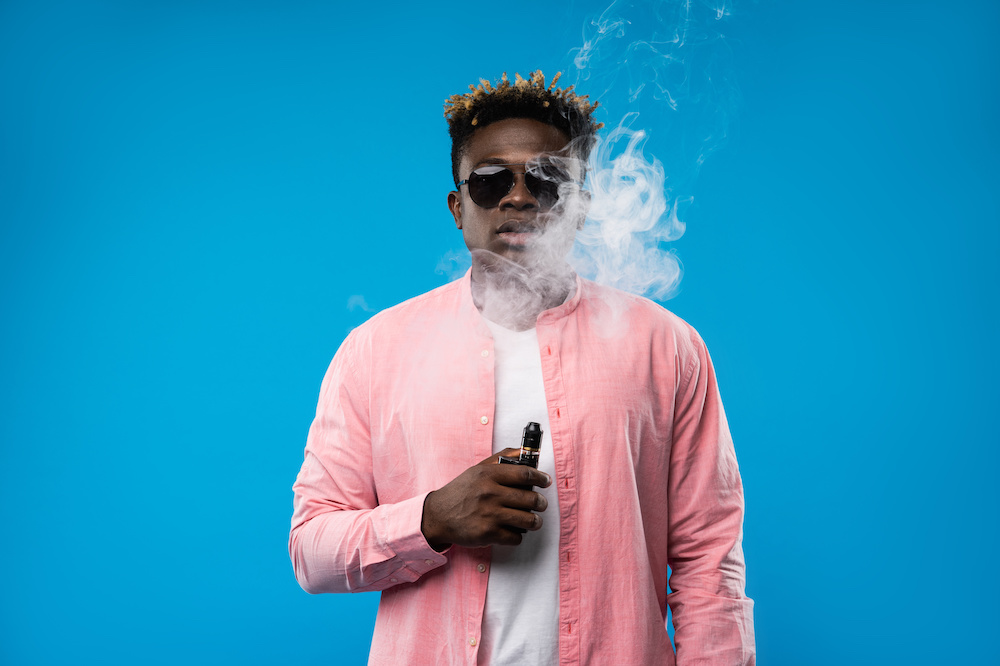 Young man with dreadlocks smoking electronic cigarette